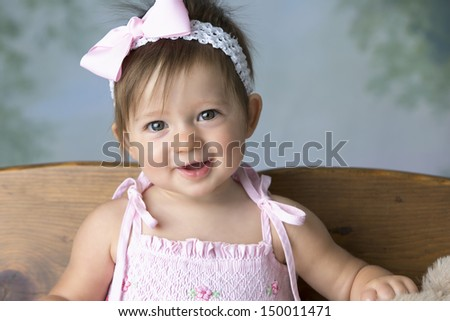 Beautiful baby girl with bow in hair smiling a happy smile - stock photo
