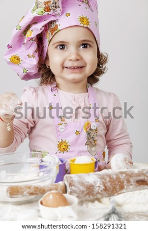 Beautiful baby girl working in the kitchen baking