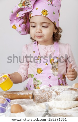 Beautiful baby girl working in the kitchen baking - stock photo