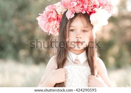 Beautiful baby girl 4-5 year old wearing peony wreath outdoors. Looking at camera. Childhood. Summer season.  - stock photo