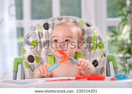 Beautiful  baby holding itself with a spoon and fork - stock photo