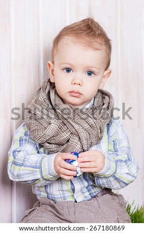 Beautiful baby in a funny scarf playing with easter egg. Child is happy and cheerful. - stock photo