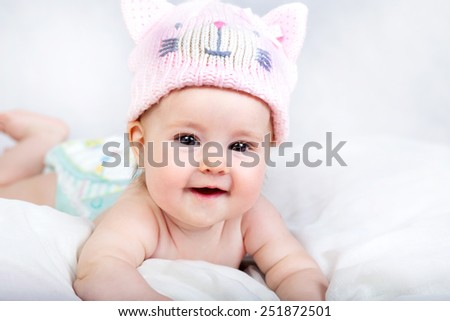Beautiful baby in funny cat hat - stock photo