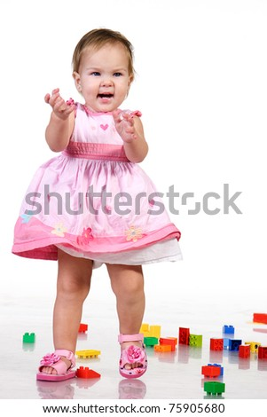 Beautiful baby in pink dress playing with colorful blocks. isolated on white