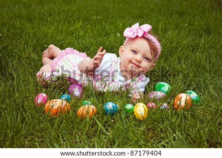 Beautiful baby laying in grass with an assortment of colored Easter eggs - stock photo