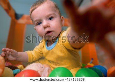 Beautiful baby lying among colorful balls reaching out for toys - stock photo