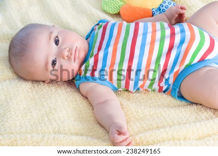 beautiful baby lying on a blanket of yellow colored - stock photo