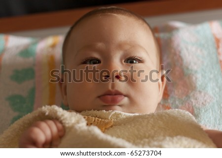 Beautiful baby lying on bed under a towel - stock photo