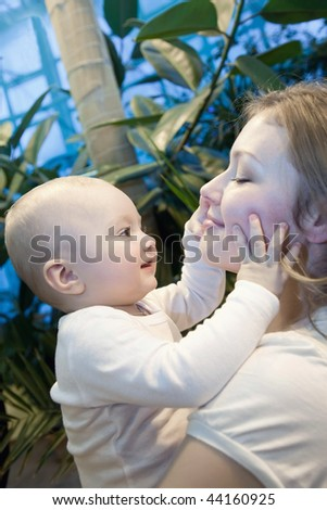 Beautiful baby of ten months old in his mothers hands. - stock photo