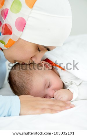 Beautiful baby of two months old in his muslim mothers hands. - stock photo