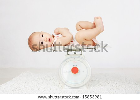Beautiful baby on on weighing scale - stock photo