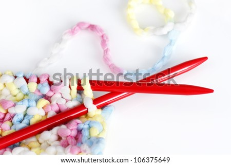Beautiful baby or arts and crafts background with red needles with pastel or baby colors wool or yarn. - stock photo