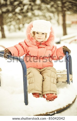 Beautiful baby playing on snow in winter park. Full length portrait, vintage toned - stock photo