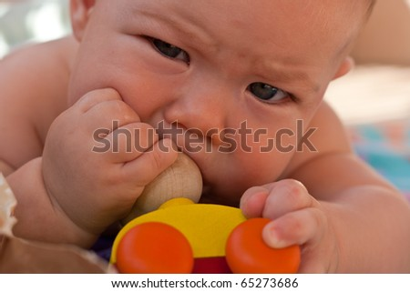 Beautiful baby playing with a toy - stock photo