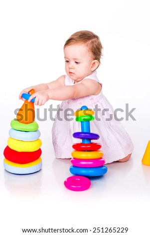Beautiful baby playing with stacking rings isolated on white - stock photo