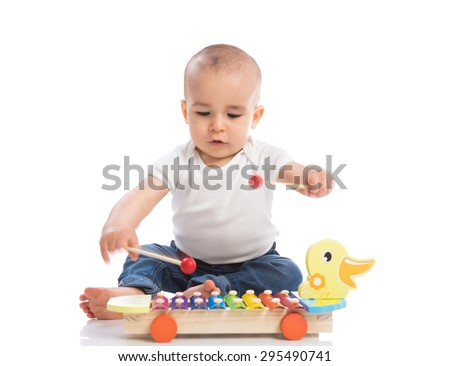 Beautiful baby sitting and playing with metallophone isolated - stock photo