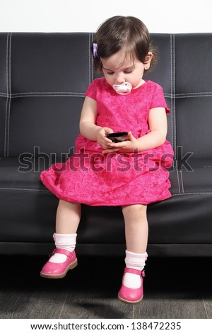 Beautiful baby sitting on a black couch at home playing with a smart phone - stock photo