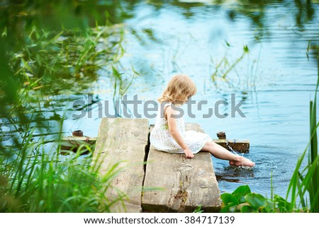 Beautiful baby sitting on the beach in a white dress. Girl looking at the water. The child  on the bridge by the river. Lots of lush greenery. - stock photo