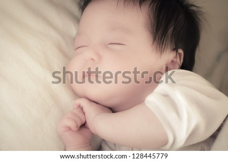 Beautiful baby sleeping on one side