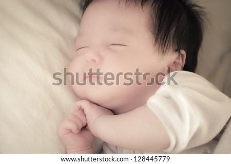 Beautiful baby sleeping on one side - stock photo