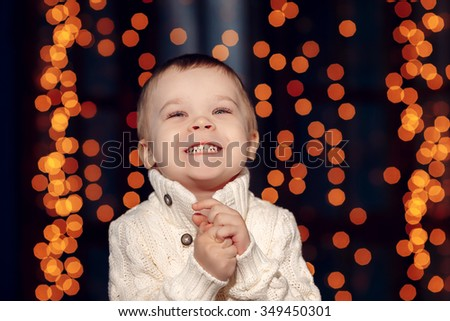 Beautiful baby smiling in the background lights garlands - stock photo