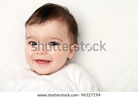 Beautiful baby smiling looking at camera - stock photo