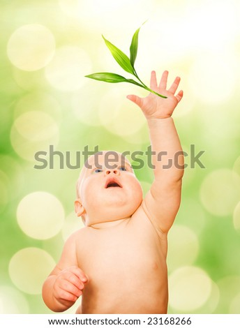 Beautiful baby trying to catch green leaf