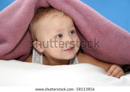 Beautiful baby under blanket - stock photo