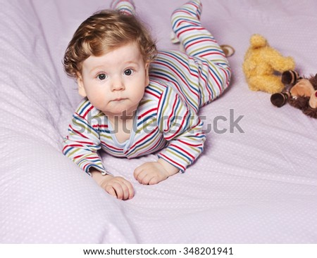 Beautiful baby with a lovely toy. The child in the crib.