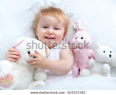 beautiful baby with  a toys lying in white bed