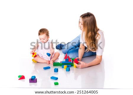 Beautiful baby with mother building a castle with cubes isolated on white - stock photo