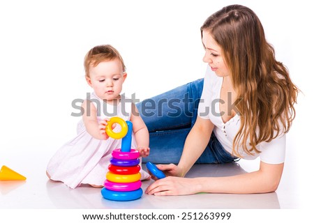 Beautiful baby with mother playing with stacking rings isolated on white - stock photo