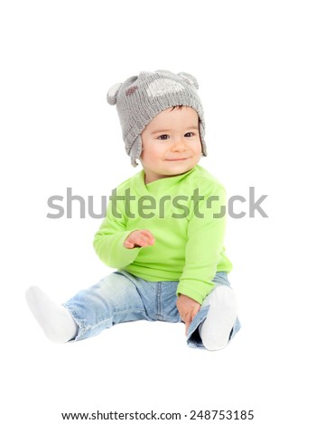 Beautiful baby  with wool hat sitting on the floor isolated - stock photo