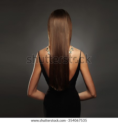 beautiful back of young woman in a black sexy dress.luxury.beauty brunette Girl with a necklace on her back - stock photo