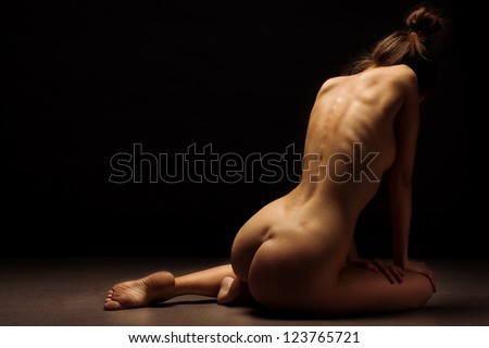 Beautiful back of young woman over dark background - stock photo