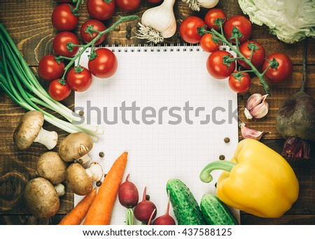 Beautiful background healthy organic eating. Studio photography the frame of different vegetables and mushrooms with a white sheet of paper on the old brown boards with free space