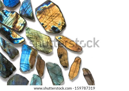 Beautiful background image with mix of natural colorful labradorite gems on the white background. - stock photo