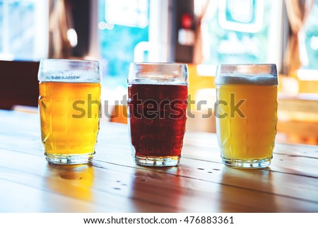 Beautiful background of the Oktoberfest. Glasses of cold fresh white, light and dark beer on the wooden bar counter in the pub. Assorted alcohol in a Flight Ready for Tasting