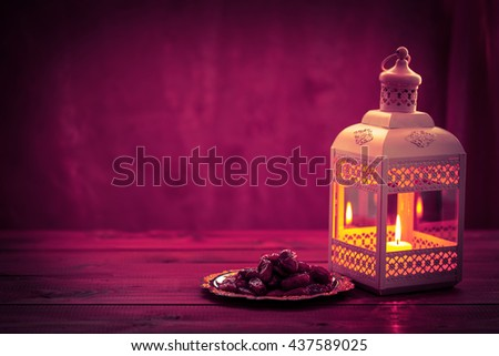 Beautiful background with a shining Fanus lantern and dried dates on a tray. The Muslim feast of the holy month of Ramadan Kareem. Free space for your text