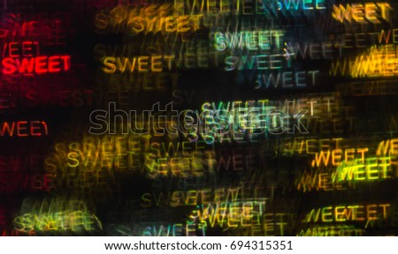 Beautiful background with different colored word sweet, abstract background, sweet shapes on black background, blurry