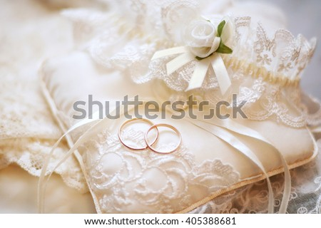 Beautiful background with wedding rings, pillow and garter