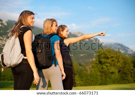 Beautiful backpackers - Three beautiful girls on a trip with backpacks - stock photo