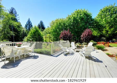 Beautiful backyard deck with white wicker table set, fire pit and chairs.