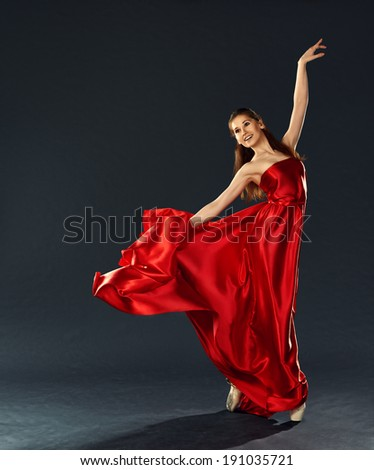 beautiful ballerina dancing a long red dress flying and in pointe - stock photo