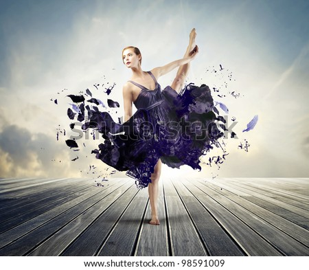 Beautiful ballerina dancing on a wood floor with her dress melting away