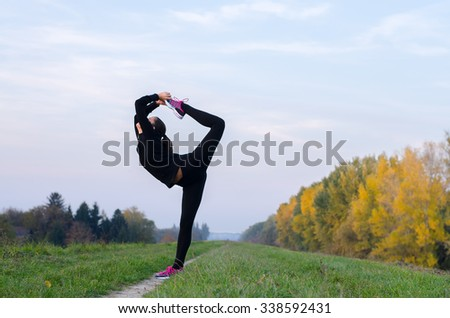Beautiful ballerina dancing outdoor on sunny autumn day. - stock photo