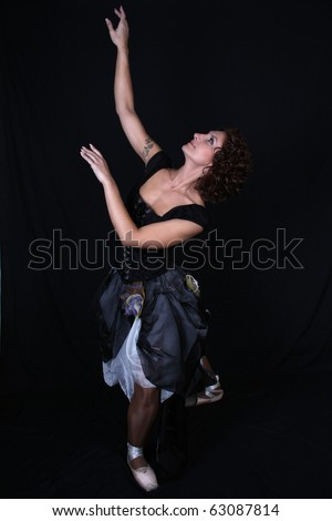 beautiful ballerina in black dress over dark background