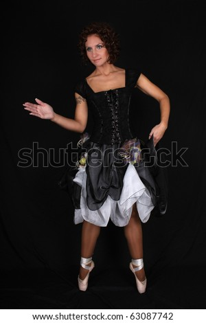 beautiful ballerina in black dress posing over dark background