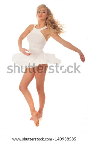 Beautiful ballerina pirrouetting twirling on her toes with her short white skirt flaring out in the air around her isolated on white - stock photo