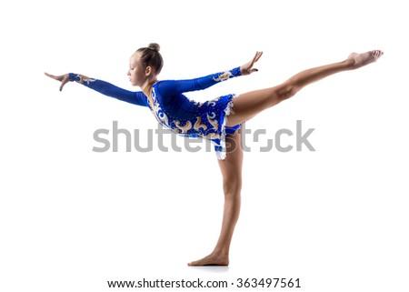 Beautiful ballerina teenage girl wearing dancer blue leotard working out, dancing, posing, doing balance art gymnastics exercise, standing on one leg, studio, white background, isolated - stock photo